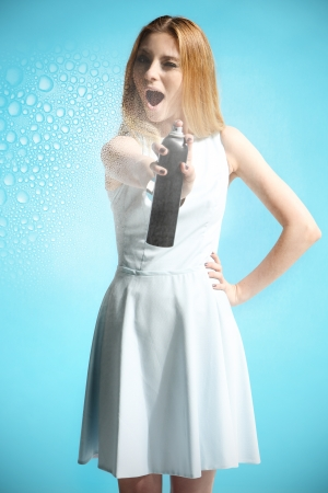hairspray: Beautiful girl in a white dress holding a bottle with hairspray