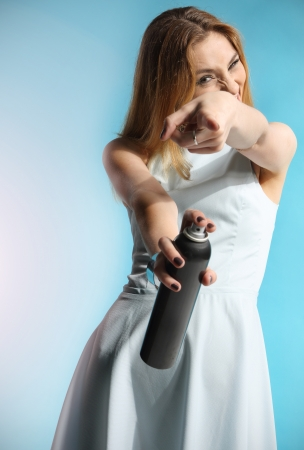 Beautiful girl in a white dress holding a bottle with hairspray  photo