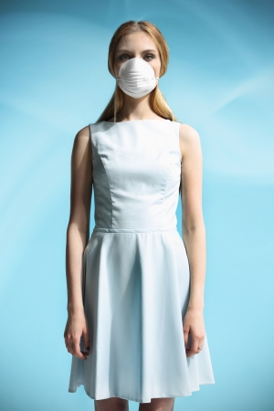 Beautiful girl in a white dress with a respiratory mask on her face photo