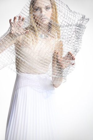 captivate: Beautiful girl in a white dress covered with a mesh isolated on white background