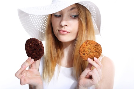 Cute young woman eats cookies on the white background photo