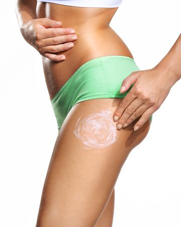 muslos: Mujer masajear la crema en el muslo