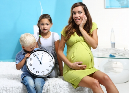 mother and children with a big clock Stock Photo - 22419199