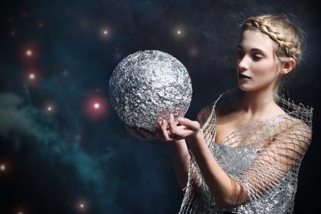 Vrouw die een zilveren kogel tegen de sterrenhemel Stockfoto - 22848407
