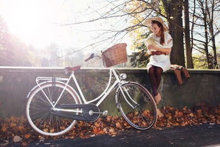 romantic autumn girl sits on bridge and reads the book photo