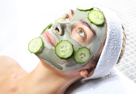 woman relaxes in the mask with green clay and cucumber  photo