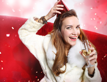 hat new year s eve: Beautiful girl with a glass of champagne greets the New Year  Stock Photo
