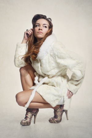 Fashion model in elegant white fur coat and gold shoes  photo