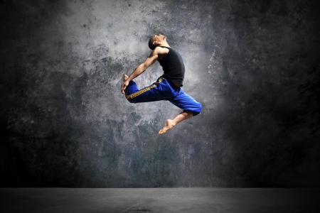 Young dancer is jumping on stage