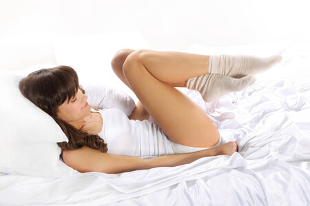 Beautiful woman resting in a soft, white linen photo