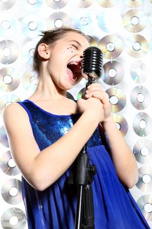 Meisje in een blauwe jurk zingen karaoke