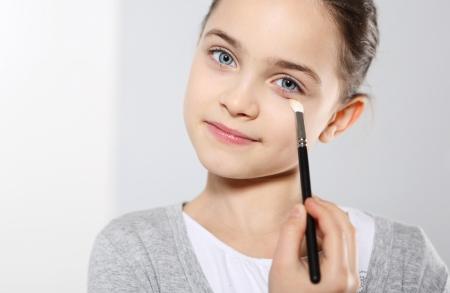 adulthood: A teenage girl applying eye shadow