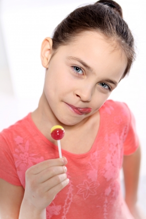 Young girl in a pink shirt with lollipop