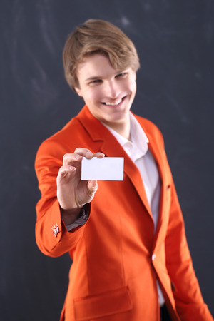 Joyful boy in orange jacket with white card photo