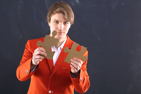 Man in orange suit holding puzzle pieces photo