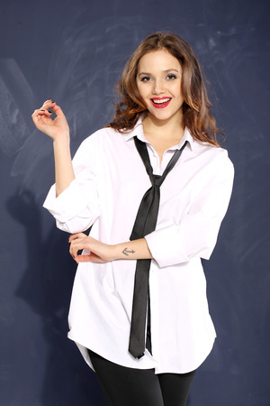 shirt unbuttoned: Young beautiful woman in a man s shirt unbuttoned on the background of school board Stock Photo