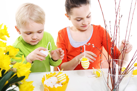 decorates: Siblings decorates Easter eggs  Stock Photo