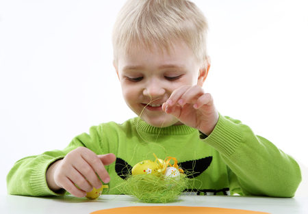 decorates: Green Easter - a little boy decorates Easter eggs  Stock Photo