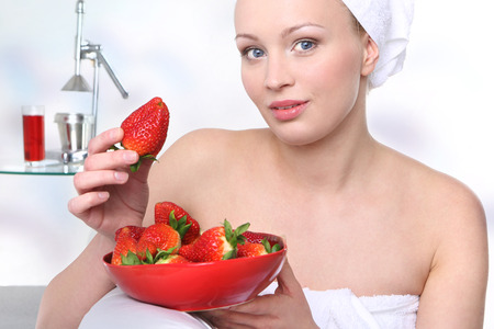admires: Attractive girl with a bowl of ripe strawberries relaxes in the living room