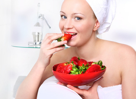 admires: Diet strawberry  Attractive girl with a bowl of ripe strawberries relaxes in the living room