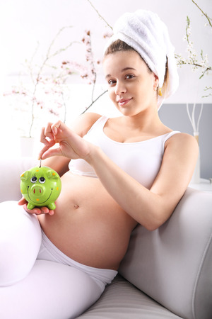 savings problems: Pregnant with piggy bank  Pregnant woman crosses the savings to the green piggy bank sitting on a sofa