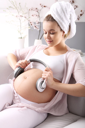 s stomach: Music in pregnancy  A pregnant woman lets the music for belly relaxing on a sofa