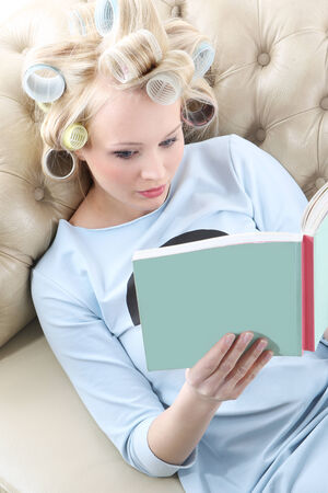 Relax with a nice book  Young woman with hair rollers screwed reading a book while relaxing on the sofa photo