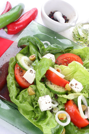 Salad with fresh vegetables Salad with lettuce, tomato, cucumber, onion, olives clearing sauce   photo