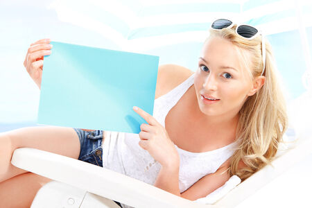 Beautiful blonde woman sitting on a lounger beach holding a blue sign with space for text  photo