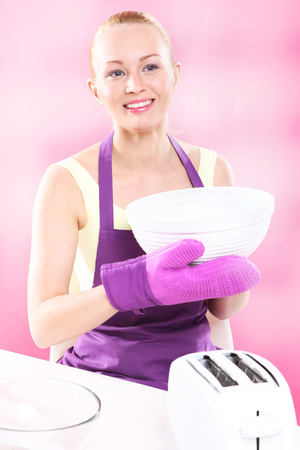 Joyful cooking  Young, attractive housewife cooks food in a pink kitchen  photo
