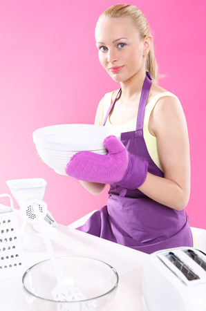 Kitchen fashion  Young, attractive housewife cooks food in a pink kitchen  photo