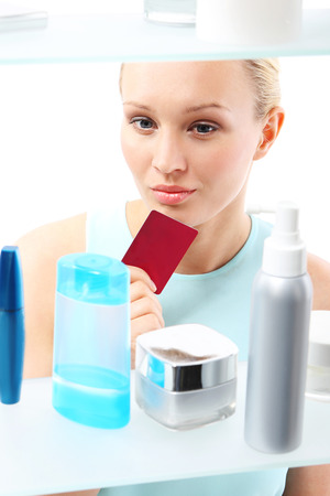 decides: Shopping at the drugstore  A woman with a card club buys cosmetics  Stock Photo