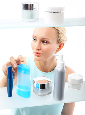 Woman in shop chooses cosmetics  A woman stands at the client shelf and selects cosmetics    photo