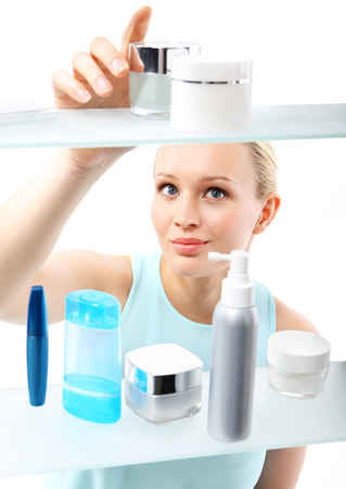 Shopping in perfumery  A woman stands at the client shelf and selects cosmetics    photo