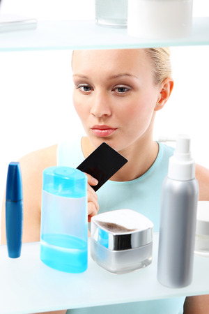 decides: Woman buying cosmetics in drugstore  A woman with a card club buys cosmetics  Stock Photo