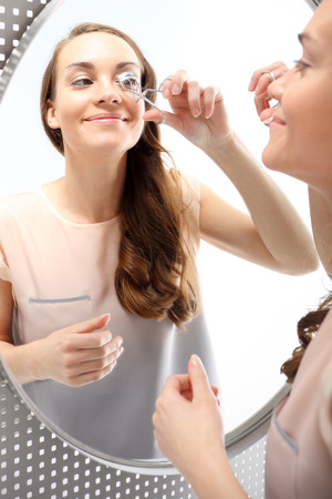 attaches: Woman curls lashes eyelash curler  Portrait of a woman that curls lashes standing in front of a mirror