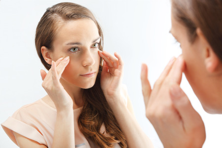 anti wrinkles: Mimic wrinkles ,signs of skin aging First wrinkles  Portrait of a peer-reviewed in the mirror   Stock Photo