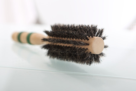 ead:  Round brush for styling hair   Hair styling accessories piled on the bathroom shelf   Stock Photo