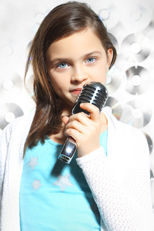 Gifted child Child, teen, girl, singing into a microphone, a small singer photo
