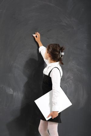 Carino bambina in piedi da un consiglio scolastico nero Archivio Fotografico