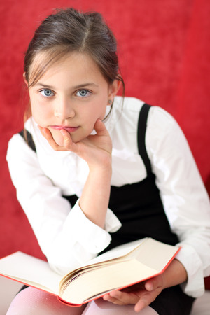 maturation: girl reading a book sitting on the chair