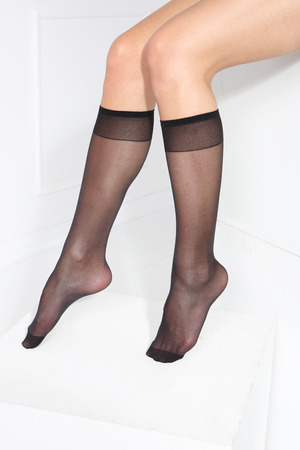 Female legs in tights, stockings, socks on a white background