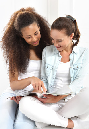 Happy women learn to read a book.  Two happy women reading a book. photo