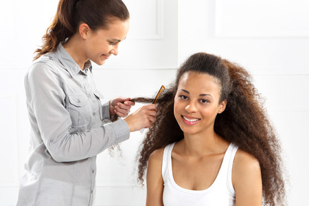 comb hair: Hairdresser  African woman at the hairdresser