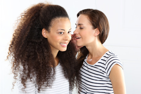 Two cheerful friend.  Two young women whisper in his ear. photo