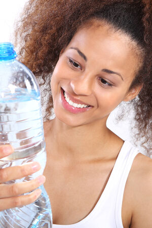 Mineral water, dark skinned girl with bottle of water photo