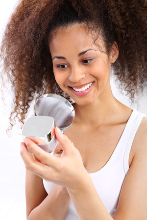dark skinned: Dark skinned woman reads the face cream. Young dark skinned girl smiling while looking under the microscope the face cream