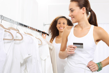 shoes off: Woman in clothing store pay credit card.