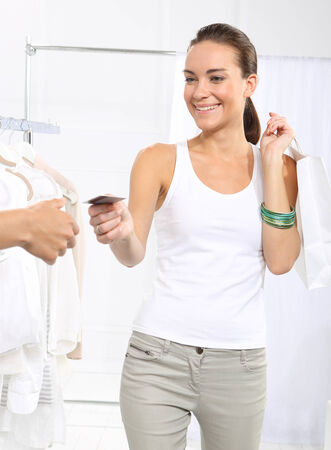 pay for: Woman in clothing store pay for purchases by credit card.