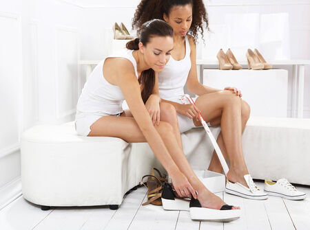 shoes off: Women try and buy shoes at a shoe store, mulatto and Caucasian